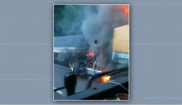 #Pracegover Na foto, a cabine em chamas e o pai tentando tirar o filho