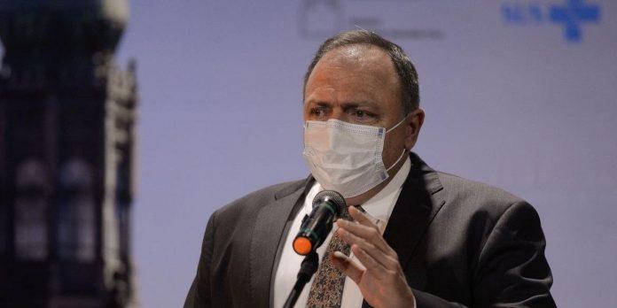 #Pracegover Fot: na imagem há um homem de terno preto, camisa branca e de máscara. Há também um microfone