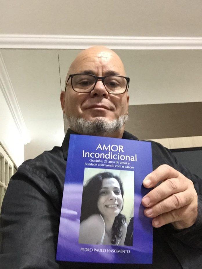 #Pracegover Na foto, Pedro Paulo Nascimento aparece segurando o livro com a foto de Gracinha