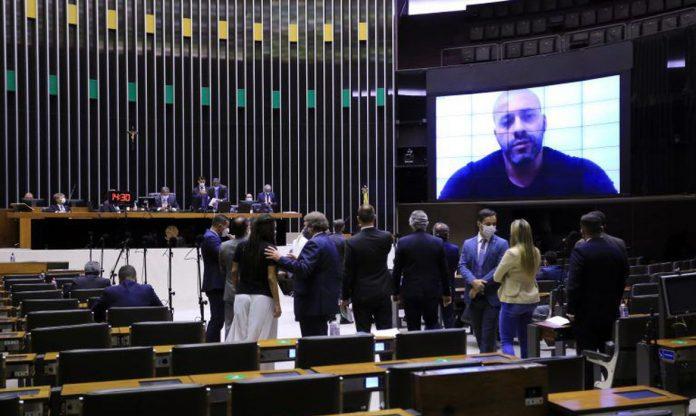 #Pracegover Foto: na imagem há um deputado no telão, há pessoas próximas em pé e outras sentadas
