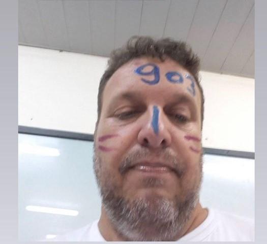 #Pracegover Foto: na imagem há um homem com barba grisalha e com o rosto, o nariz e a testa riscado de canetinha