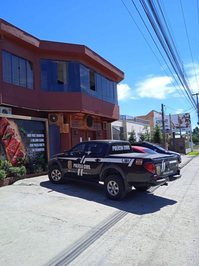 #pracegover Na foto, viaturas da polícia em frente ao frente ao estabelecimento interditado