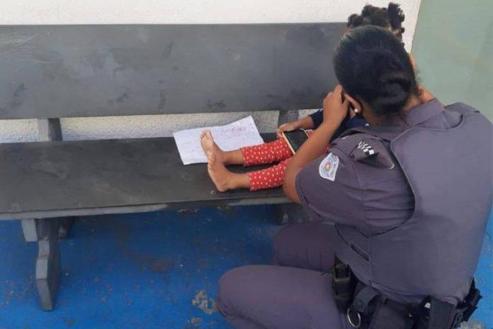 #Pracegover Na foto, aparece a perna da menina e uma policial cuidando dela.