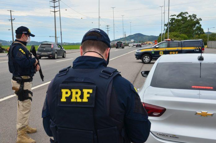 #pracegover Na foto, agente da PRF durante fiscalização na BR 101