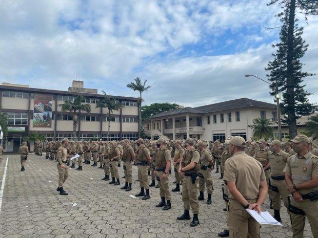 #Pracegover Foto: na imagem há muitos policiais militares, prédios e árvores