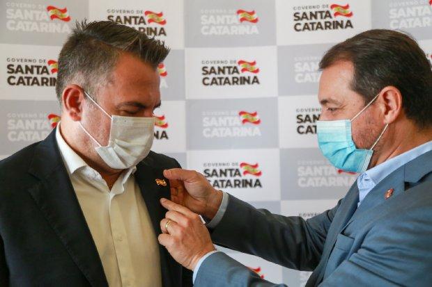 #Pracegover Foto: na imagem há dois homens de máscara