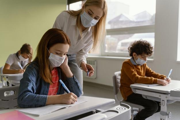 #pracegover Na foto, estudantes e uma professora usando máscara, dentro de sala aula mantendo distanciamento