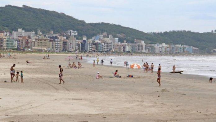 #Pracegover Na foto, banhistas na praia do Mar Grosso