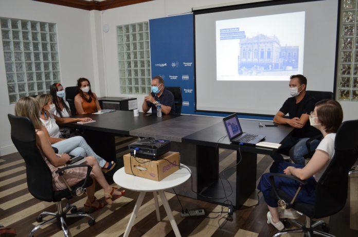 #Pracegover Foto: na imagem há uma mesa, um computador e algumas pessoas em reunião