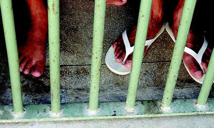#Pracegover Foto: na imagem há os pés e pernas de duas pessoas. Umadelas está com um calçado branco e a outra com os pés no chão