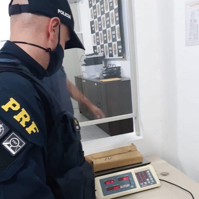 #Pracegover Na foto, um agente de PRF pesando em uma balança as drogas apreendidas