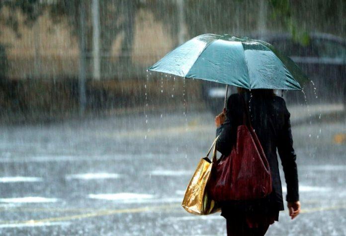 #Pracegover Na foto, uma mulher com um sombrinha andando sob a chuva
