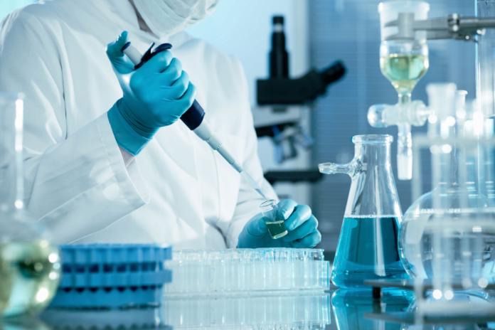 #Pracegover Foto: na imagem há experimentos químicos e uma pessoa de jaleco