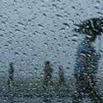 #pracegover Na foto, pingos de chuva em um vidro e ao fundo silhueta de pessoas caminhando com guarda-chuva