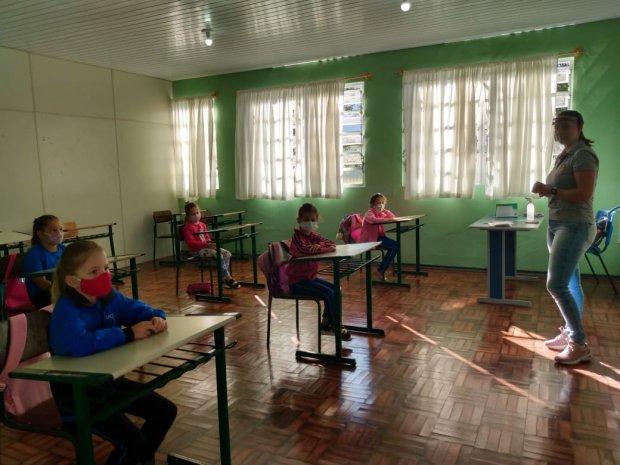 #pracegover Na foto, alunos e uma professora em sala de aula, todos com máscara e mantendo distanciamento