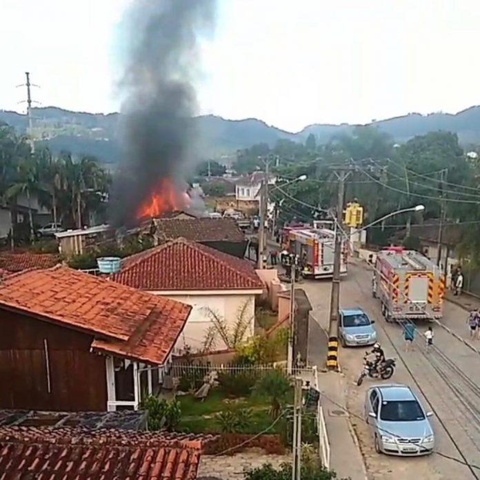 #Pracegover Na foto, uma estrada com vários carros passando e ao fundo uma residência em chamas