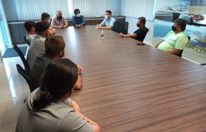 #Pracegover Foto: na imagem há várias pessoas reunidas, uma mesa e uma cadeira