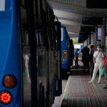 #Pracegover Foto: na imagem há ônibus, pessoas e uma estrutura de concreto