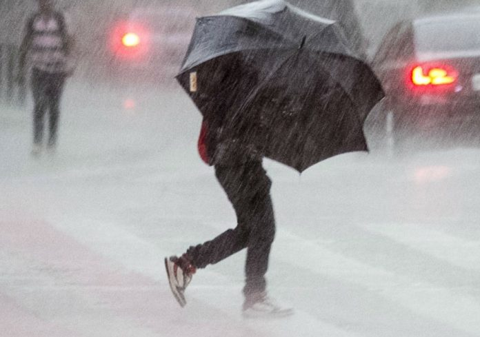 #Pracegover Na foto, uma pessoa segurando uma sombrinha e atravessando a rua sob forte chuva
