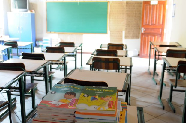 #Pracegover Foto: na imagem há uma sala de aula com muitas carteiras e alguns livros sobre a mesa