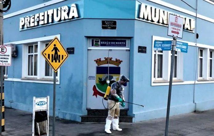 #Pracegover Na foto, a fachada da prefeitura de Braço o Norte e um profissional fazendo higienização na calçada