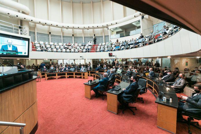 #Pracegover Foto: na imagem há cadeiras, pessoas, computadores