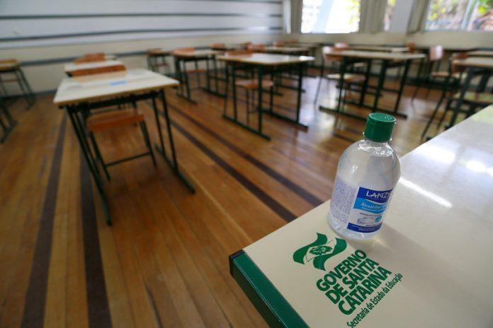 #Pracegover Na foto, uma sala de aula com carteiras vazia, destaque para um frasco de álcool em gel sobre uma mesa.