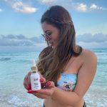 #Pracegover Foto: na imagem há uma mulher com um produto de beleza nas mãos. Ela está em uma praia