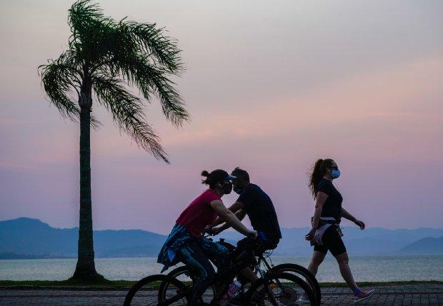 #Pracegover Na foto, pessoas pedalando e uma mulher caminhando na beira-mar em Florianópolis