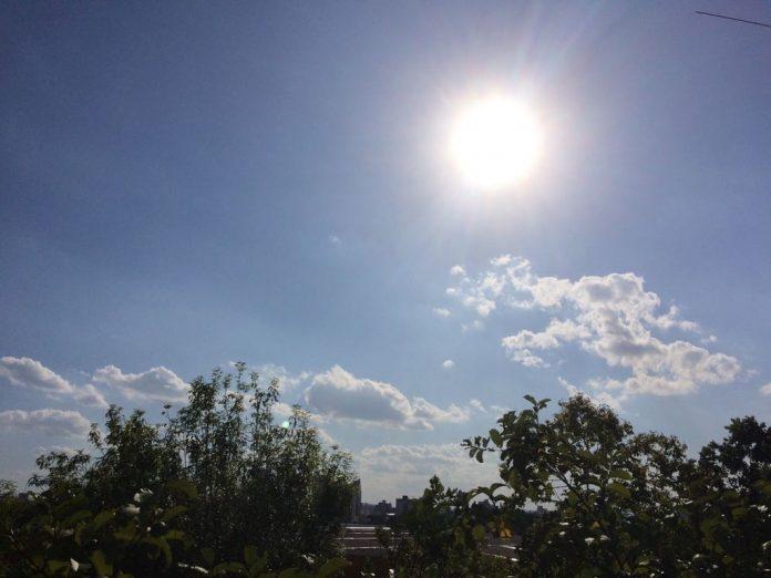 #pracegover Na foto, céu claro com a presença de sol e nuvens