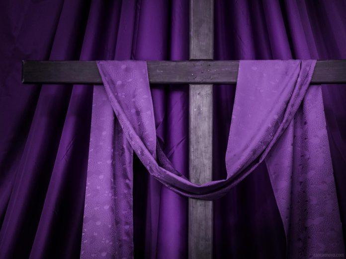 #Pracegover Foto: na imagem há uma cruz e tecidos roxo
