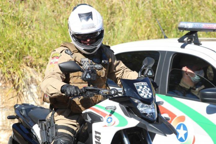 #Pracegover Foto: na imagem há um homem em uma moto de polícia e do lado uma viatura da polícia