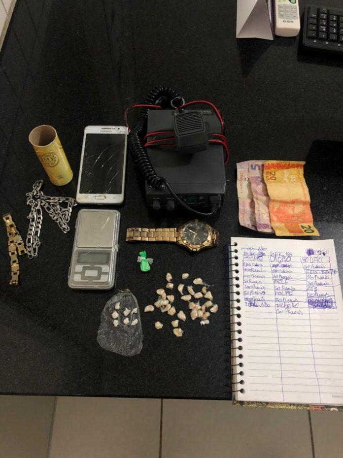 #Pracegover Foto: na imagem há relógio depulso, celular, um caderno de anotações, pulseiras, dinheiro e outros itens