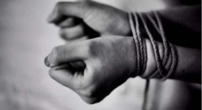 #pracegover Na foto, uma pessoa com as mãos amarradas com uma corda