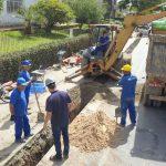 #pracegover Na foto, homens estão em volta de um buraco em uma estrada e ao lado há máquinas e caminhão