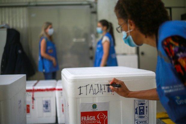 #Pracegover Na foto, caixas de isopor com a vacina sendo demarcadas com os locais de distribuição
