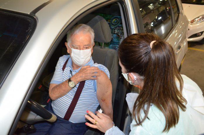 #Pracegover Foto: na imagem há um idoso sendo vacinado e uma mulher aplicando a vacina. Ele está dentro de um carro