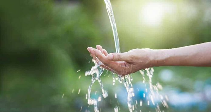#Pracegover Na foto, água caindo sobre a mãe de uma pessoa