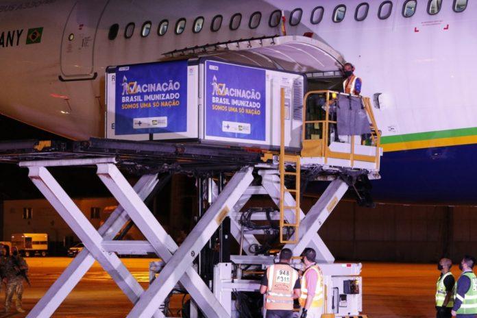 #Pracegover Na foto, uma plataforma elevadiça colocando equipamentos dentro do avião do Governo Federal para trazer vacina da Índia