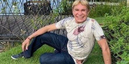 #Pracegover Foto: na imagem há um homem sentado no gramado