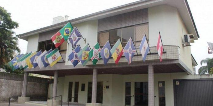 #Pracegover Foto: na imagem há um edifício de dois pavimentos, bandeiras, portas e janelas