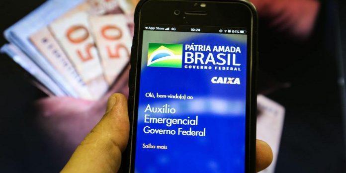 #Pracegover Foto: na imagem há uma mão, um celular e dinheiro