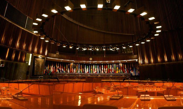 #Pracegover Foto: na imagem há microfones, bandeiras, mesas e luzes