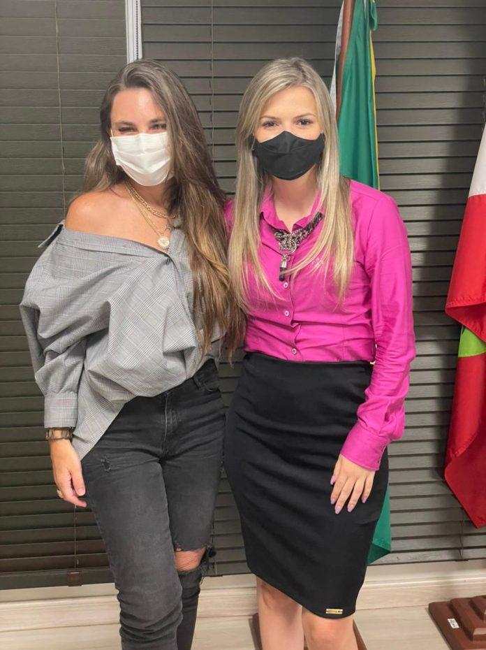 #Pracegover Foto: na imagem há duas mulheres de máscara e hpróximo a elas há duas bandeiras, a do Brasil e de Santa Catarina