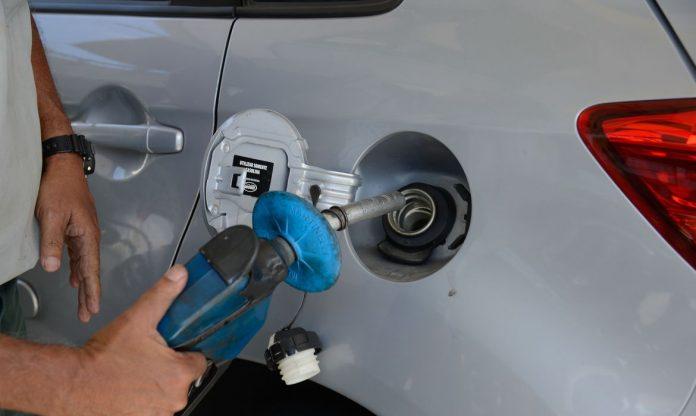 #Pracegover Foto: na imagem há um veículo, uma mão e uma bomba de gasolina