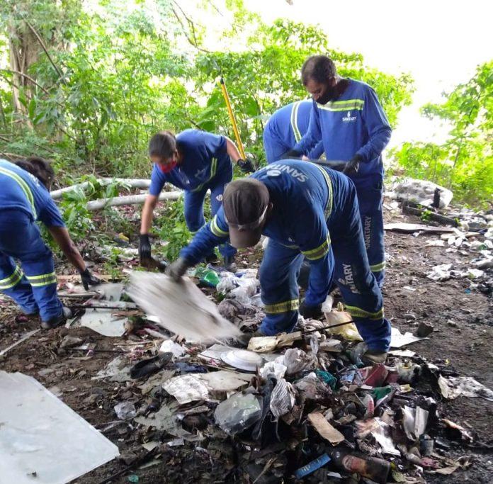 #Pracegover Foto: na imagem há homens recolhendo lixos no chão deixados por outras pessoas