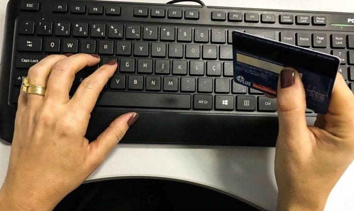 #Pracegover Foto: na imagem há um teclado de computador, duas mãos, um anel e um cartão de banco
