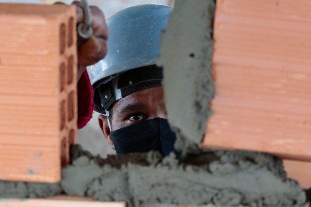 #Pracegover Foto: na imagem há um homem de capacete, tijolos e massa de concreto