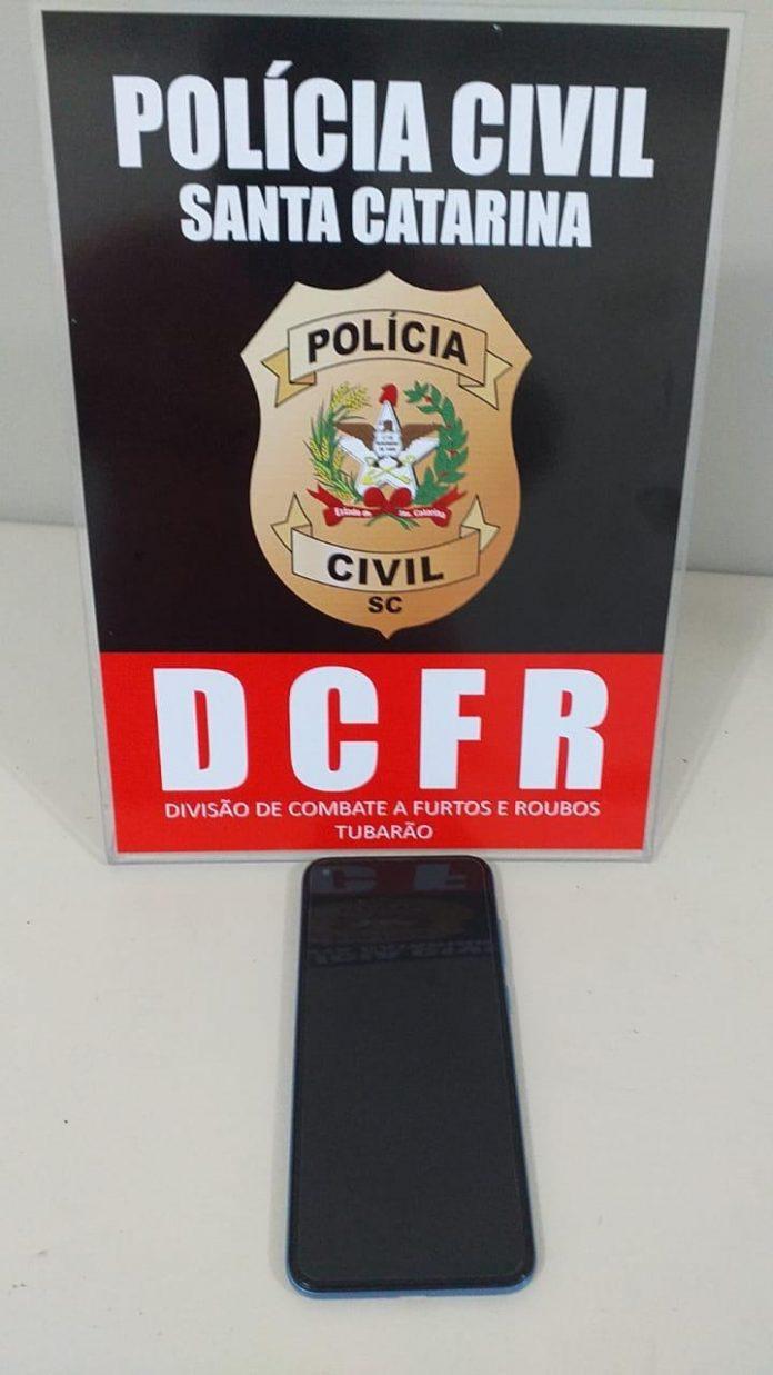 #Pracegover Foto: na imagem há uma placa e um celular