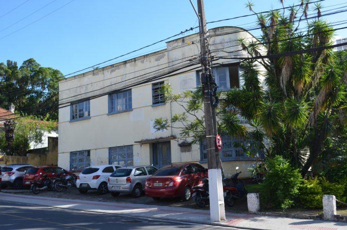 #Pracegover Foto: na imagem há um edifício, carros e árvore